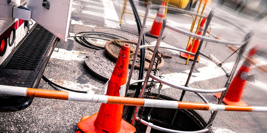 Underground Construction with construction cones and underground manhole lids with cabling truck above