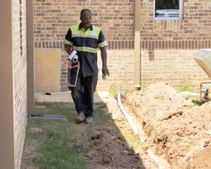 Man walking beside ditch with cable pipe