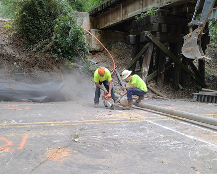 men cut through the road for underground cable construction