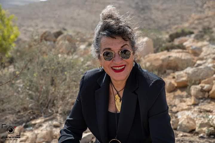 אירית יושבת עם בלייזר שחור ותכשיטים מחייכת עם משקפי שמש