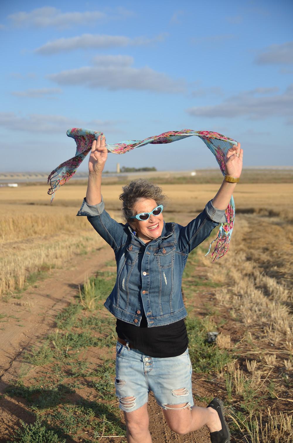 אירית רצה בשדות עם צעיף מעל הראש מורם בשתי ידיה צילום מאירה גוראי רז