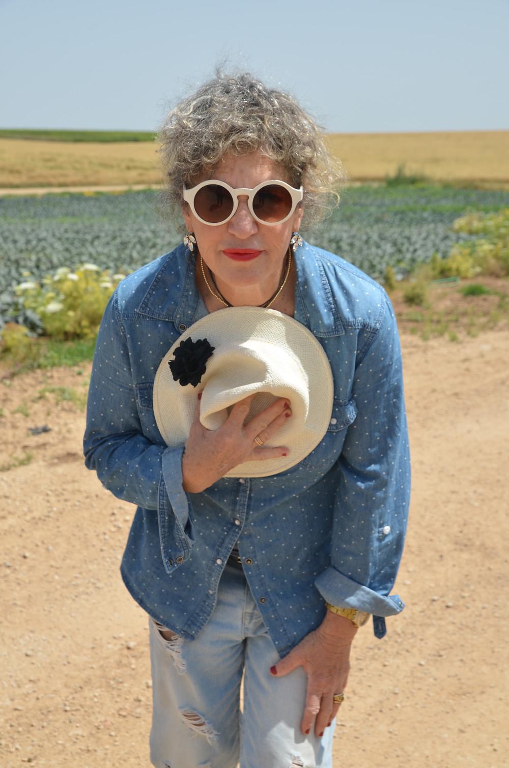 אירית משתחווה מחזיקה כובע בסמוך  לחזה צילומם מאירה