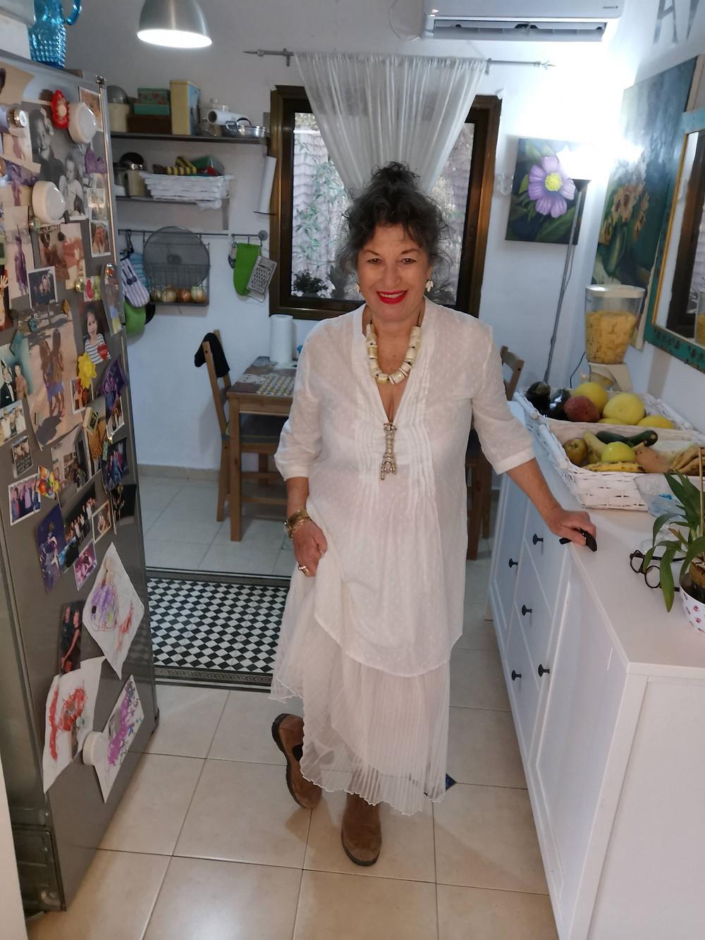 אירית לובשת חצאית לבנה וחולצה לבנה ופריטים בהתאמה שרשרת לבנה ועגילים לבנים