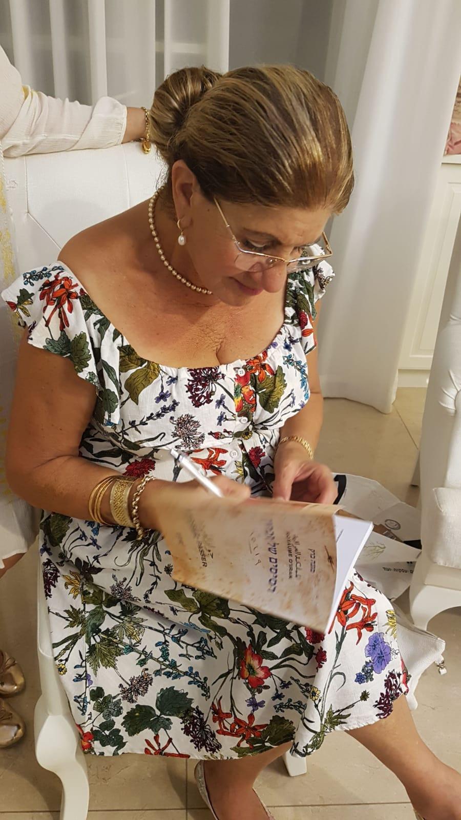 מונה ברק חותמת על ספר השירה שלה רסיסים
