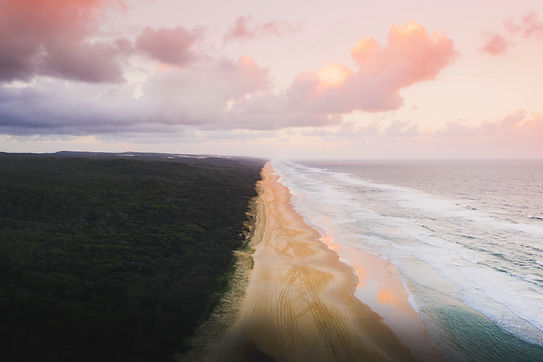 drone-view-of-coastline-under-pastel-pink-sky.jpg