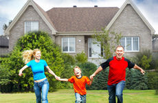 Family trio running on lawn in front of house