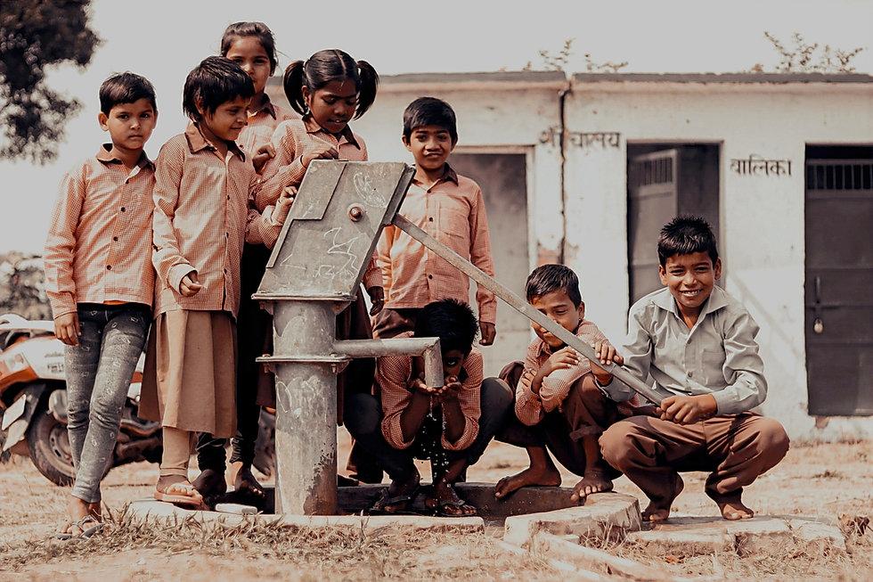 children-standing-next-to-manual-water-p