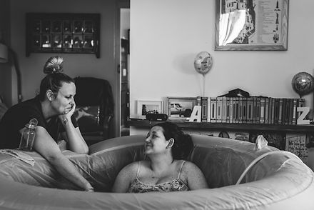 Homebirth midwife with mum in birth pool