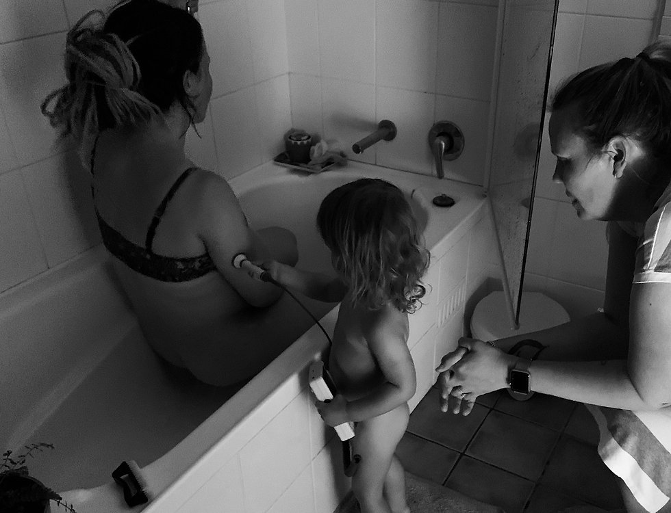 Homebirth midwife with pregnant mother in bath and child watching on
