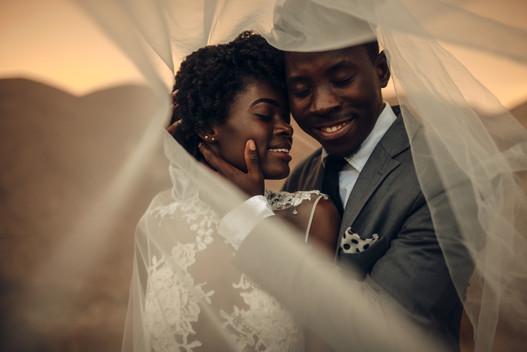 Black happy newlyweds stand under bridal