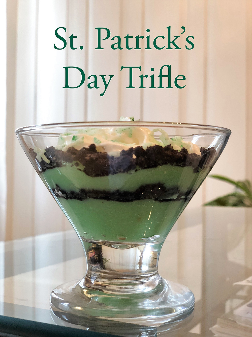 St. Patrick's Day trifle with alternating layers of green pudding and Oreo crumbs, topped with green shredded coconut.