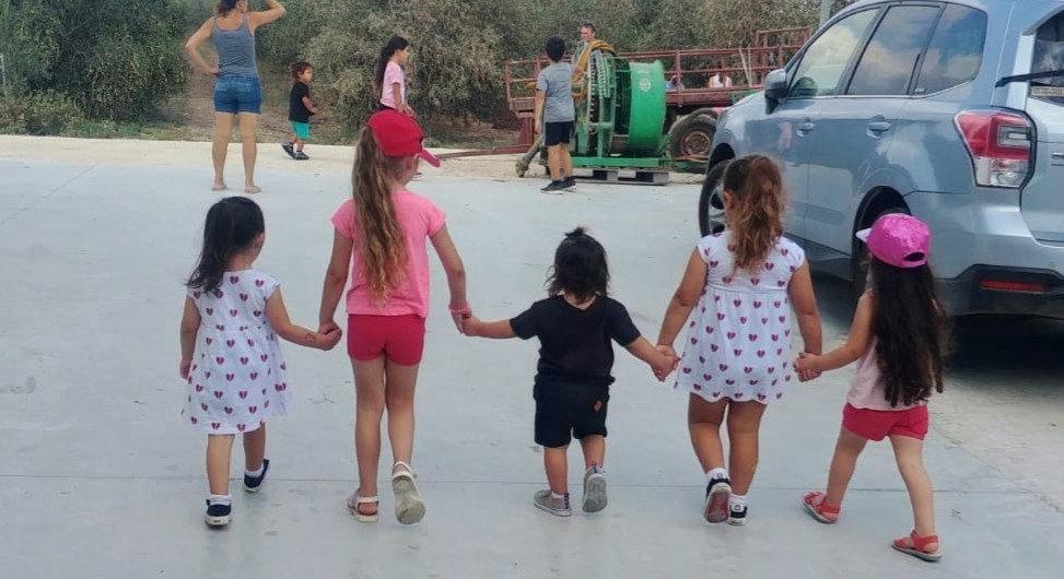 ילדים מבקרים בבית הבד ומחזיקים ידיים