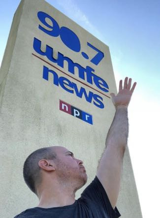 Mark Baratelli, Publisher of The Daily City, stands in front of the WMFE 90.7 Public Radio sign in a half-Evita pose.