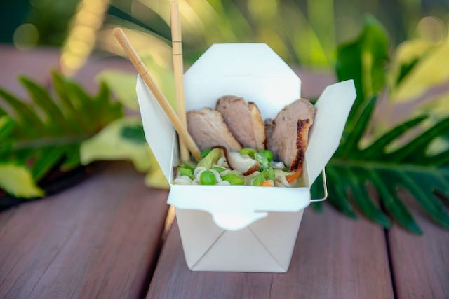 A white take-out carton filled with slices of duck and vegetables and ramen