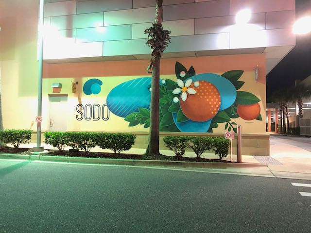 SODO Mural with large oranges and lots of blue colors and green cleaves with the SODO logo in modern tall lettering in black