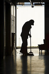 Silhouette of a man moping warehouse flo