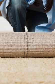 A close-up of a rug being unrolled by a woman. Only the woman's jeans, part of her pale blue blouse and some strands of her long dark hair are visible behind the rolled-up rug.