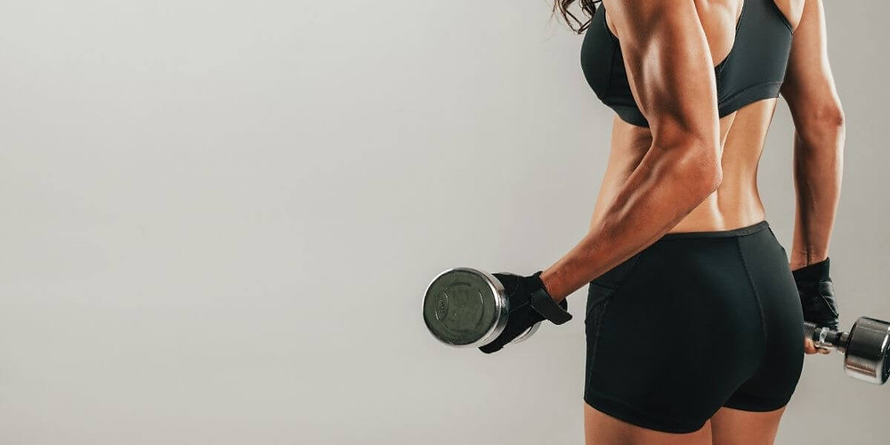 Female athlete lifting weighs and flexing muscles.