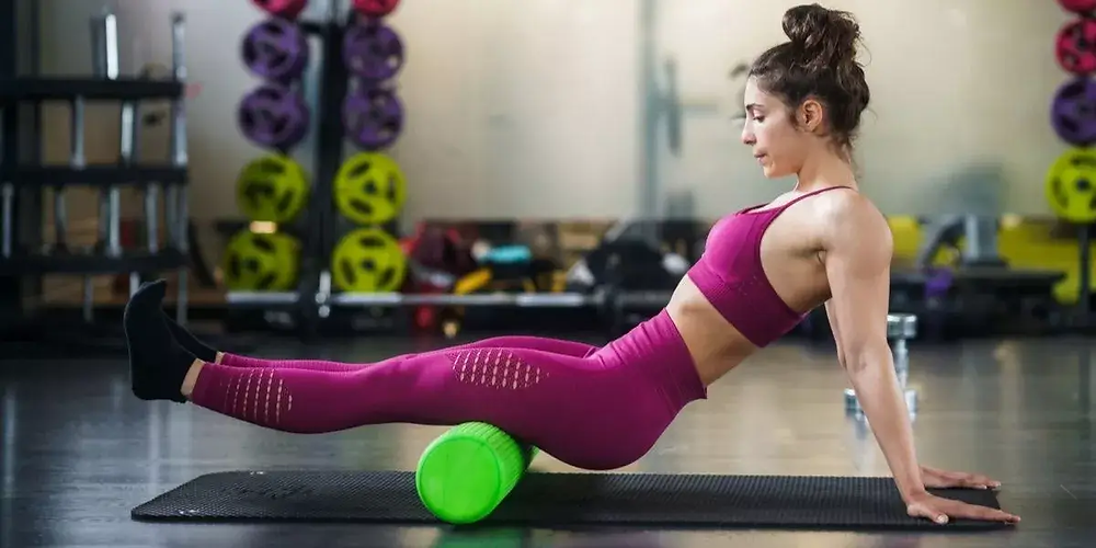 Athlete using a foam roller for muscle recovery.