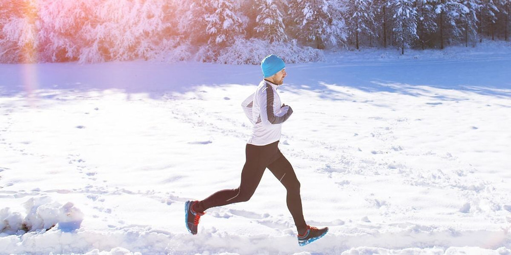 Athlete running through snow wearing cold weather running tights.