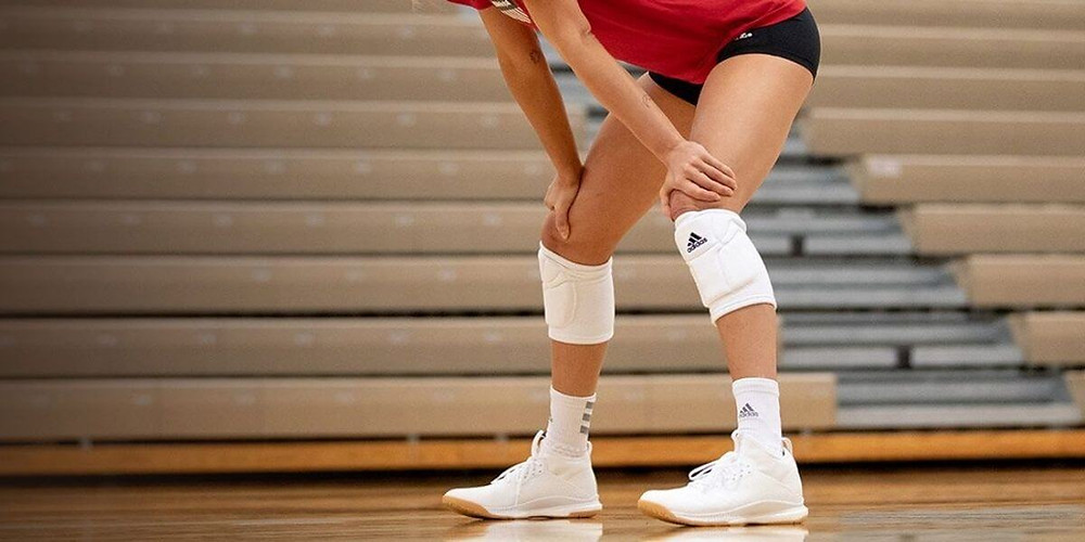 Volleyball player in ready position wearing volleyball shoes.