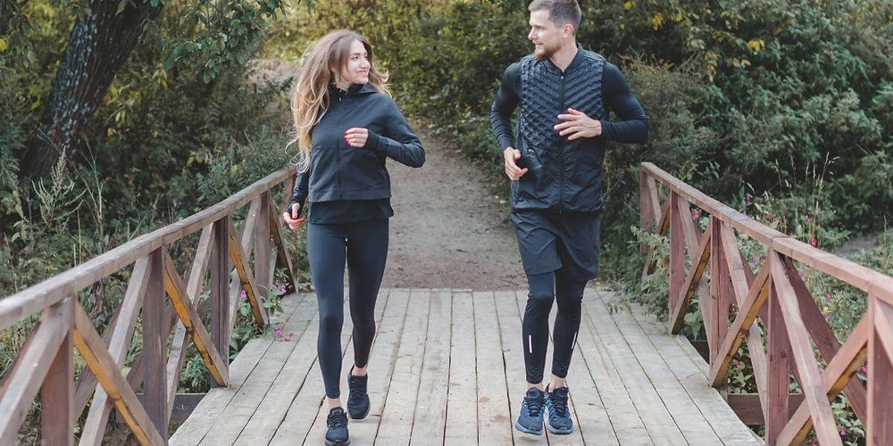 Male and female running together wearing compression tights.