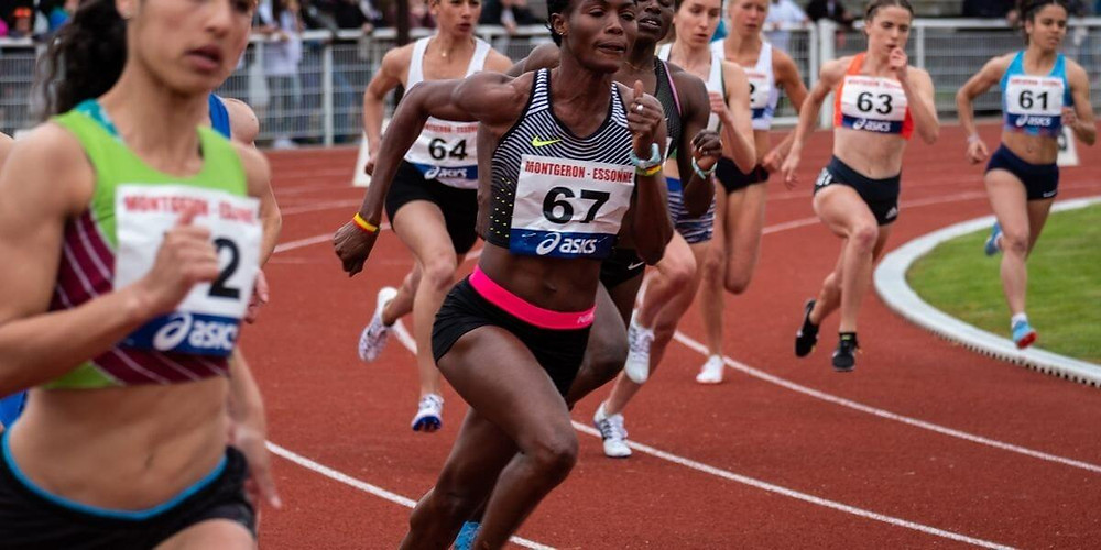 Female track athletes competing in compression running shorts.