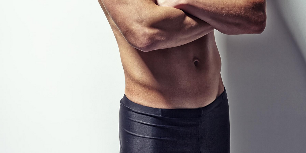 Athlete with folded arms wears compression shorts as underwear.
