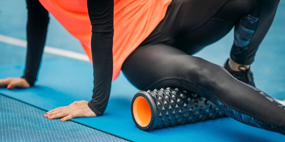 Athlete wearing compression tights and foam rolling for muscle recovery.