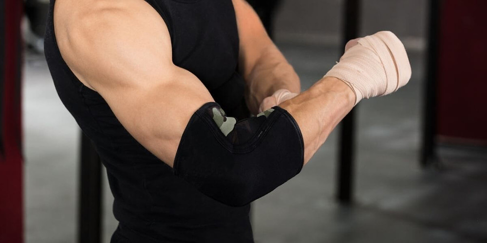 Weightlifter wearing compression elbow sleeve.