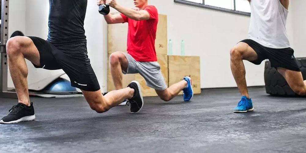 Three male athletes training at the gym.
