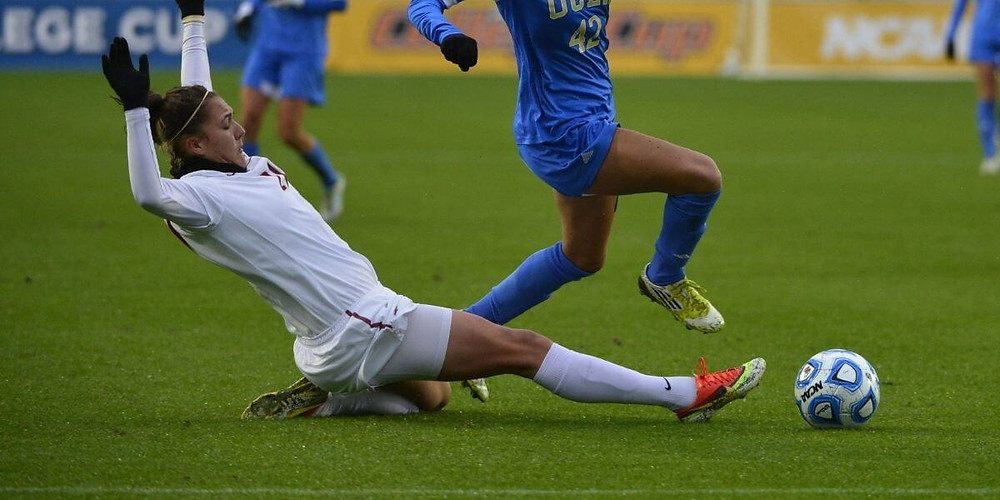 Female soccer player wearing compression shorts sliding for ball.
