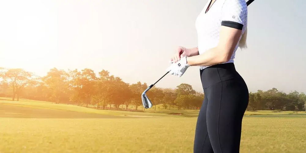 Female golfer wearing leggings while playing golf.