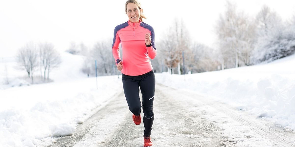 Woman running in cold weather wearing compression running tights.