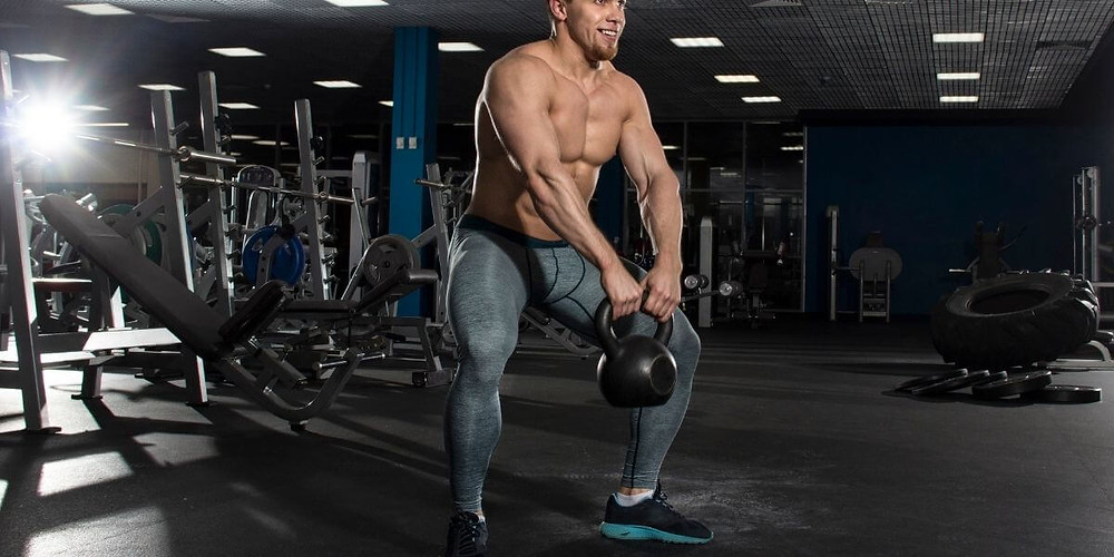 Male athlete wearing compression tights lifting weights at gym.