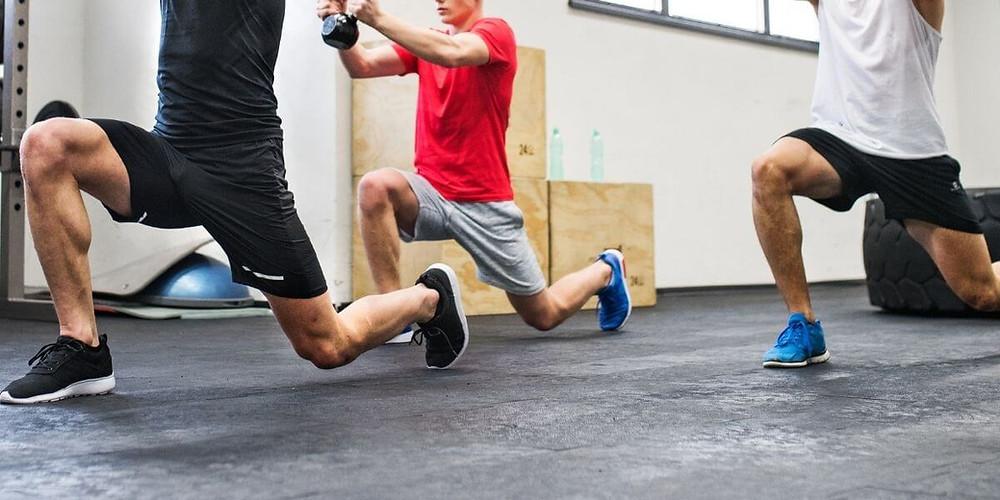 Three male athletes exercising.
