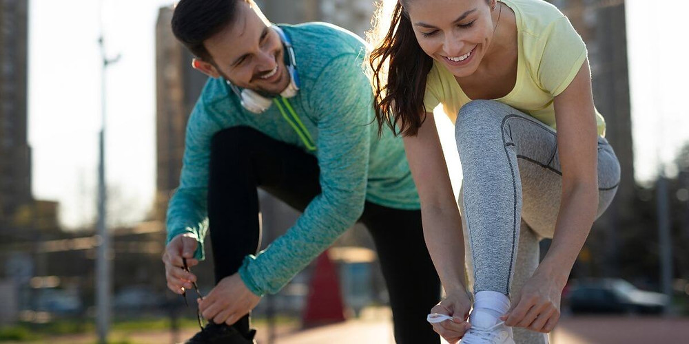 Smiling man and woman wearing compression wear.