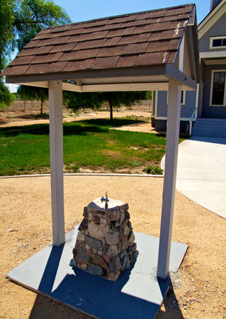 Drinking fountain in front of historic schoolhouse.