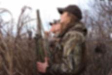 Women duck hunting in talll grass