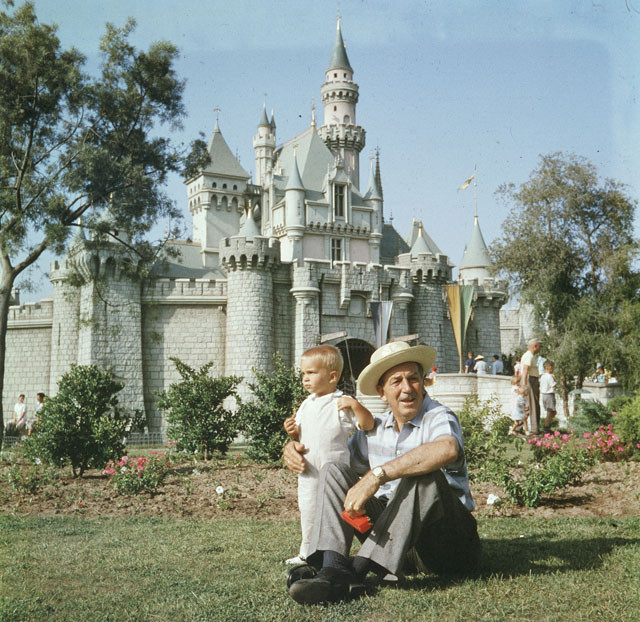 Walt sitting with his grandson in front of the magic kingdom, Disney Land. Source: Google