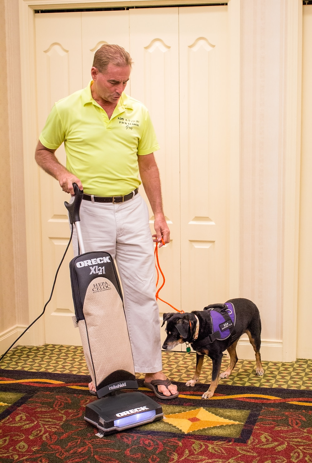 Greg with Bella teaching her not to attack the vacuum cleaner