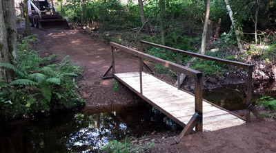 A trail & bridge through the woods at Demon Acres