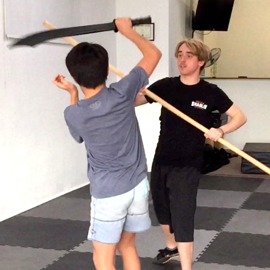 Kwan and Cassidy sparring with sword and bo staff