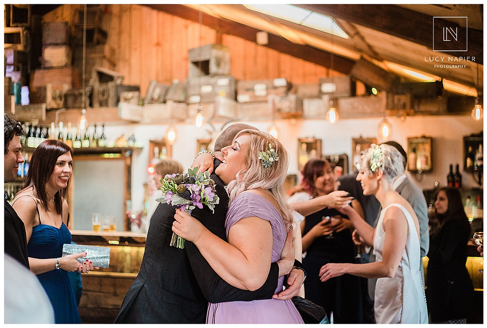 Bridesmaid hugs a guest after the wedding ceremony