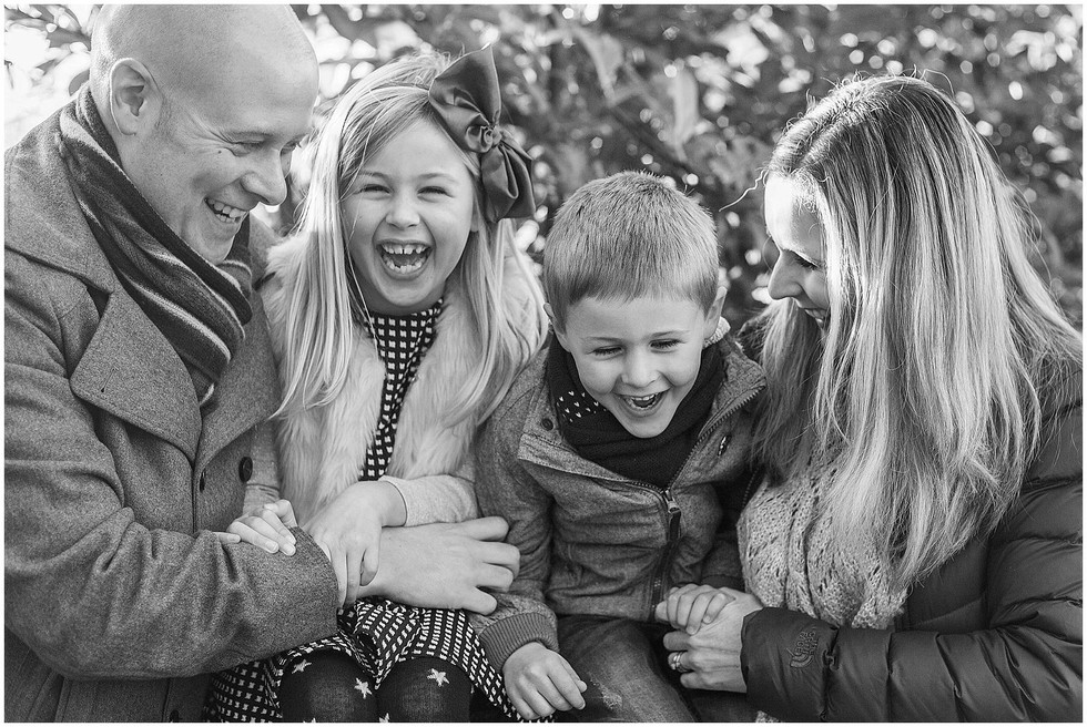 a family laughs together in the park
