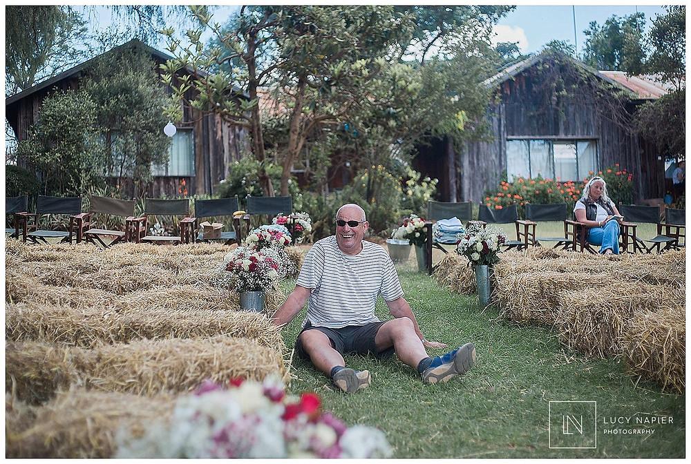 A man sits amongst hay bales