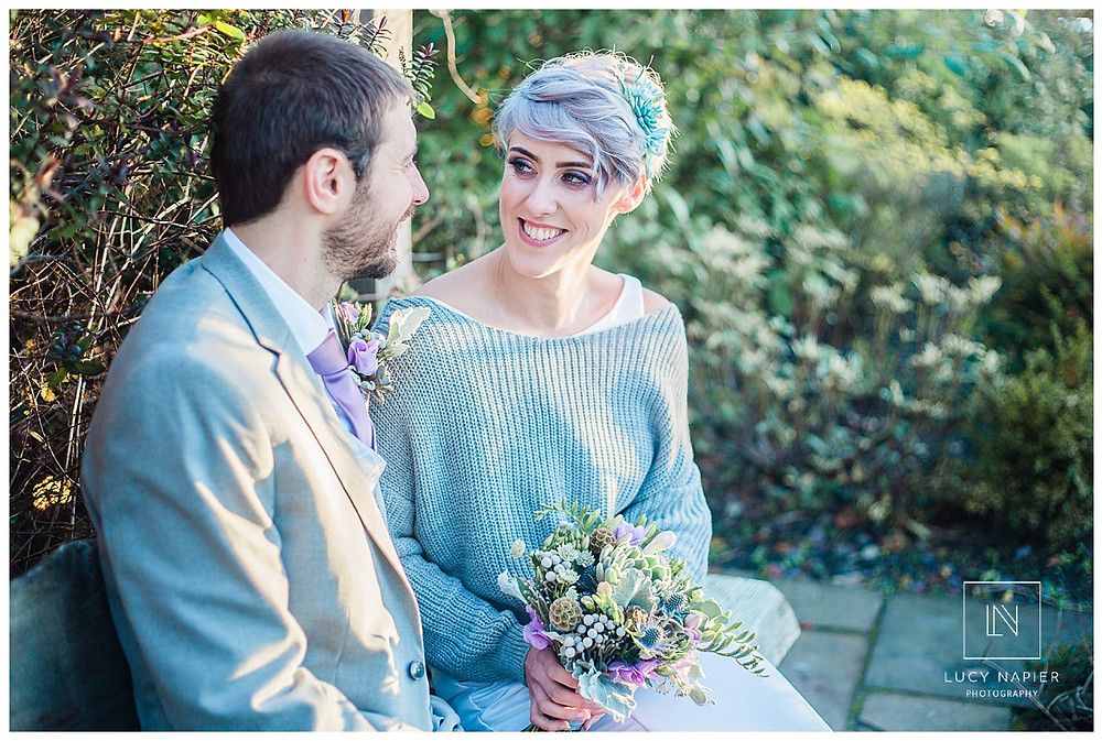 The bride and groom enjoy a relaxing moment together on a bench
