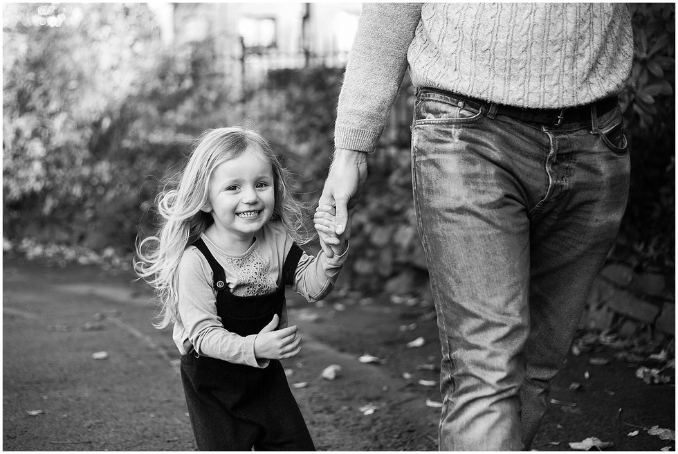 little girl in black and white walking with her dad