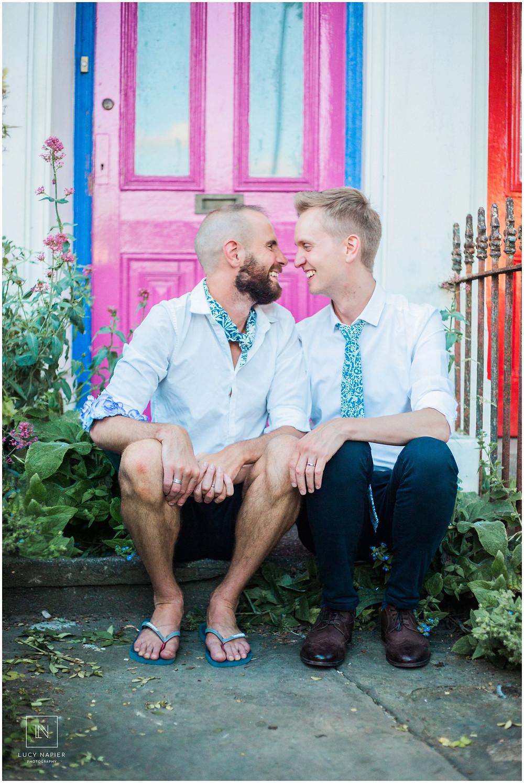 two grooms posing in front of a pink door in London.