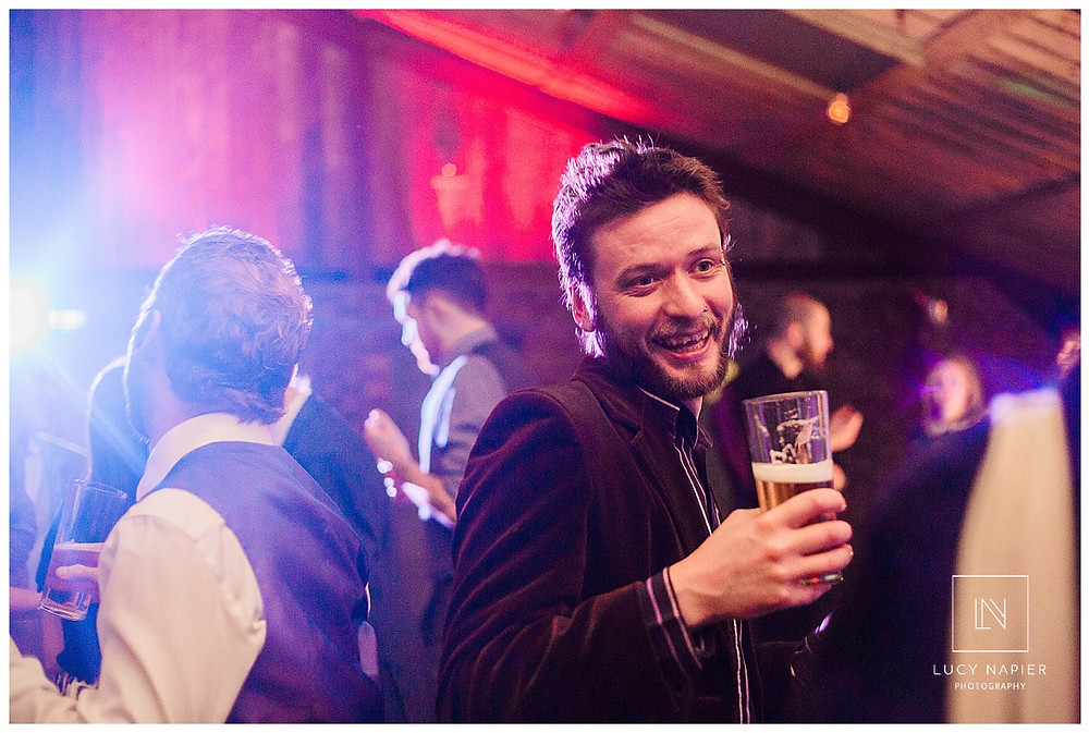 a guest dances at Owen House Wedding Barn with a pint in his hand